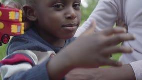 Portret positieve Afrikaanse Amerikaanse vrouw die met haar weinig zoon spelen die plastic stuk speelgoed in het park gebruiken D stock video