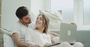 Portret potomstwa dobiera się rozkaz coś używa notatnika obsiadanie na kanapie i oba w piżamach zdjęcie wideo