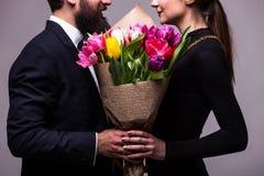 Portret potomstwa dobiera się w miłości z kwiatami tulipany pozuje przy studiiem ubierającym w klasyku odziewają na popielatym ba Obraz Stock