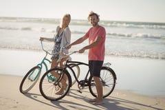 Portret potomstwa dobiera się z bicyklami stoi przy plażą Fotografia Royalty Free