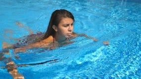 Portret potomstwa garbnikujący kobiety odświeżenie i dopłynięcie w pustym basenie Brunetki dziewczyna unosi się przy basenem hote zdjęcie wideo