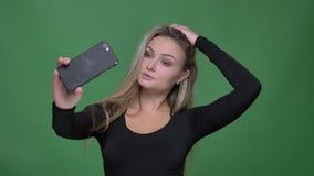 Portret potomstwa modeluje w czarnej bluzce robi fotografiom używać smartphone przy zielonym tłem zdjęcie wideo