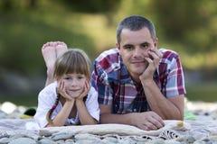 Portret potomstwa ojcuje i śliczna blond dziewczyna kłaść na pebbled r fotografia stock
