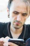 Portret potomstwa, przystojny, Kaukaski mężczyzna z stubbly brodą, używać mądrze telefon Obraz Royalty Free