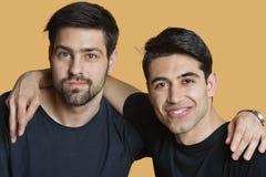 Portret potomstwo męscy przyjaciele z rękami wokoło nad barwionym tłem Zdjęcia Royalty Free