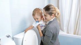 Portret potomstwo macierzysty seans jej berbecia syn dlaczego używać wezbranego guzika na toalecie Fotografia Stock