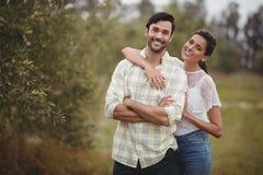Portret potomstwo pary pozycja przy oliwki gospodarstwem rolnym fotografia stock