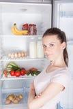 Portret poważna żeńska trwanie pobliska otwarta chłodziarka Zdjęcie Stock