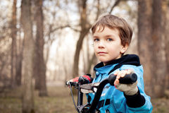 Portret poważna chłopiec z bicyklem w parku obraz royalty free
