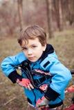 Portret poważna chłopiec z bicyklem w parku zdjęcia royalty free