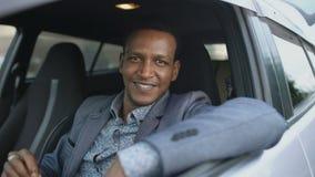 Portret poważny biznesmena obsiadanie wśrodku samochodu stawiającego okulary przeciwsłoneczni i ono uśmiecha się outdoors w kamer