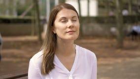 Portret poważny bizneswoman w białym koszulowym obsiadaniu w parku Fachowa kobieta ma przerwę zbiory wideo
