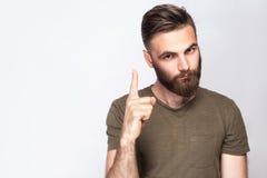 Portret poważny brodaty mężczyzna z ostrzeżenie palcową i ciemnozieloną t koszula przeciw światłu - szary tło Zdjęcia Stock