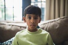 Portret poważny chłopiec obsiadanie na kanapie Zdjęcia Royalty Free