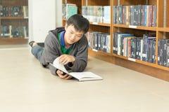 Portret poważny młody studencki czytanie książka w bibliotece Obrazy Royalty Free