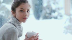 Portret powabna dziewczyna z filiżanką w rękach blisko okno zdjęcie wideo