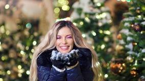 Portret powabnej śmiesznej kobiety podmuchowi płatek śniegu przy choinką zaświeca bokeh tło zbiory
