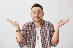 Portret powabny europejski samiec model w szkłach wzrusza ramionami zęby i pokazuje podczas gdy stojący z rozszerzaniem się podno zdjęcia stock