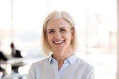 Portret pozuje uśmiecha się przy kamerą dojrzały bizneswoman obrazy stock