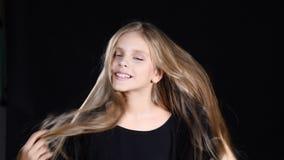 Portret pozuje urocza dziewczyna patrzejący kamerę Uśmiechający się jej włosy i dotykający Blondyn dosyć nastoletnia dziewczyna z zbiory