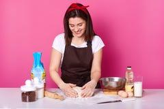 Portret pozytywna kobiet sukni bielu t koszula i fartuch, brudną twarz z mąką, ugniata ciasto, loooks zestrzela i uśmiechy, obraz stock
