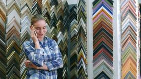 Portret pozytywny młody żeński klient patrzeje dla ramy w ramowym sklepie, opowiadający na telefonie komórkowym Zdjęcie Royalty Free