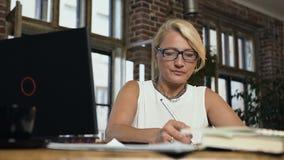Portret pracujący caucasian w średnim wieku bizneswoman używa laptop dla pisać coś w nutowej książce podczas gdy zbiory wideo