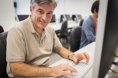 Portret pracuje na komputerze szczęśliwy profesor zdjęcie stock