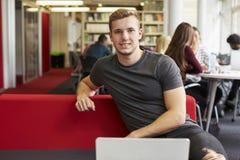 Portret Pracuje W bibliotece Męski student uniwersytetu Fotografia Royalty Free