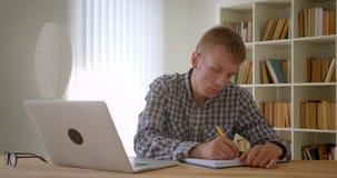 Portret pracuje z laptopem attentively i pisze notatkach na półki na książki tle caucasian biznesmen zbiory