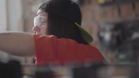 Portret professionele vrouw in een GLB en beschermende glazen met doordrongen lip en ring in neus die lengte van meten stock video