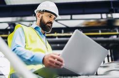 Portret przemysłowy mężczyzna inżynier z laptopem w fabryce, pracuje obraz royalty free