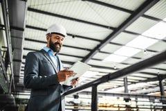 Portret przemysłowy mężczyzna inżynier z pastylką w fabryce zdjęcie royalty free