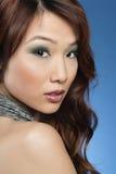Portret przyglądający nad barwionym tłem piękna młoda kobieta z powrotem Zdjęcie Royalty Free