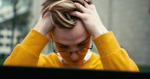 Portret przygnębiony młody człowiek w eyeglasses pracuje na laptopie plenerowym 4k materiał filmowy zbiory wideo
