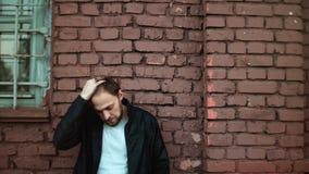 Portret przypadkowy przystojny Europejski mężczyzna Rozważna młoda samiec w skórzanej kurtce dotyka jego włosy Czerwony ściana z  zbiory wideo