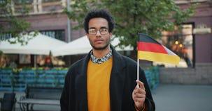 Portret przystojna amerykanin afrykańskiego pochodzenia mężczyzny mienia niemiec flaga w ulicie zbiory