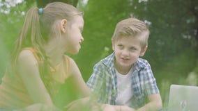Portret przystojna chłopiec urocza dziewczyna z długie włosy patrzeć w kamerę laptop w parku i Lato zbiory