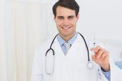 Portret przystojna lekarka trzyma zastrzyka zdjęcia stock