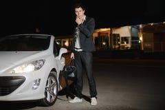 Portret przystojna mężczyzna pozycja obok jego białego kabrioletu nightlife Biznesmen w kostiumu w luksusowym samochodzie obraz stock