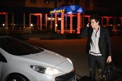 Portret przystojna mężczyzna pozycja obok jego białego kabrioletu nightlife Biznesmen w kostiumu w luksusowym samochodzie zdjęcia stock