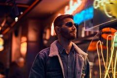 Portret przystojna mężczyzna pozycja w nocy na ulicie Iluminujący signboards, neonowi, zaświecają obrazy royalty free