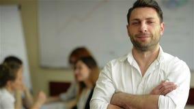 Portret przystojna młoda biznesowego mężczyzny pozycja z rękami krzyżował w biurze Mądrze caucasian młody męski projektant zbiory wideo