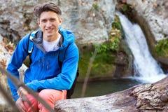 Portret przystojnego męskiego wycieczkowicza siedzący drzewny okop przy jeziorem Obraz Royalty Free