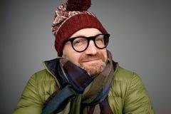 Portret przystojnego młodego człowieka zimy uśmiechnięty jest ubranym ciepły żakiet, szalik i śmieszny kapelusz, fotografia stock