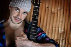 Portret przystojnego młodego modnisia mięśniowy mężczyzna opiera przeciw drewnianej ścianie i pozyci z jego gitarą Zdjęcie Royalty Free