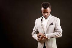 Portret przystojny afro biznesmen patrzeje zegarek na jego ręce Fotografia Stock