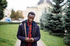 Portret przystojny Afroamerykański biznesmen używa smartphone telefon w śnieżnej jesieni miasta ulicie, pisać na maszynie wiadomo Fotografia Stock