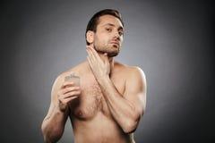 Portret przystojny bez koszuli mężczyzna używa aftershave płukankę Fotografia Royalty Free