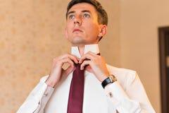 Portret przystojny biznesmen w kostiumu kładzeniu na krawacie indoors Zdjęcie Stock